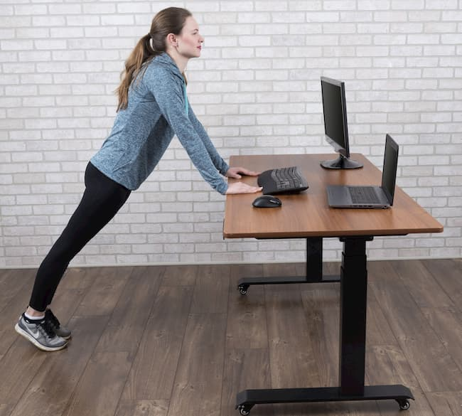 girl stretching while working ona standing desk