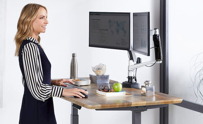 woman smiling while working on a standing desk