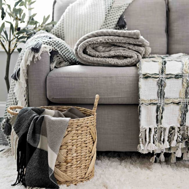 grey sofa bed with different types of throw blankets