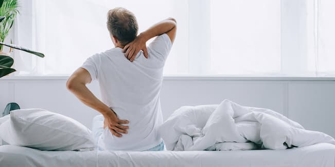 an old man sitting on a bed with back pain