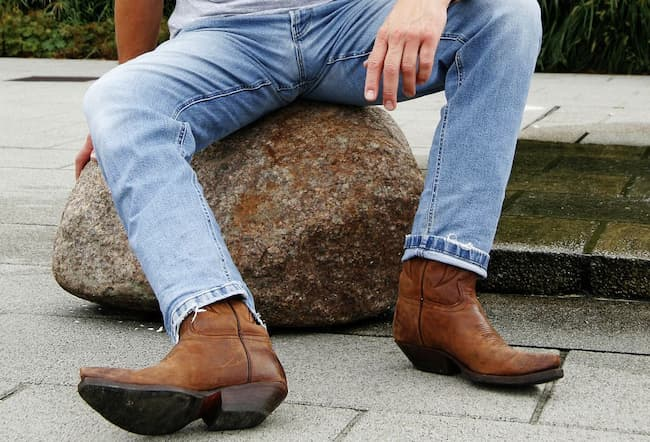 man sitting on a stone wearing blue jeans and country boots