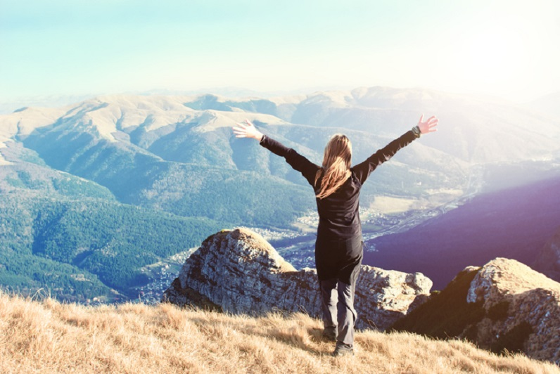 young woman standing on top of mountain with arms outstretched