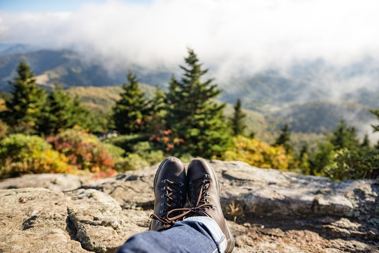 picture of a person sitting on a cliff in the woods