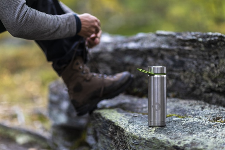 picture of person tying his boots beside a stainless steel bottle on the rocks