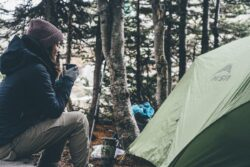 picture of a woman sitting in the woods beside a tent