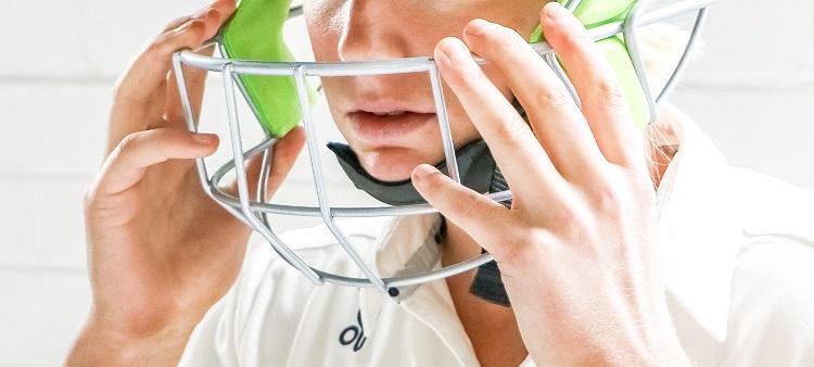 man putting on a cricket helmet