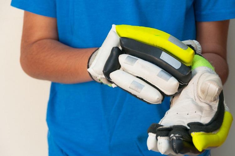 man putting on cricket gloves