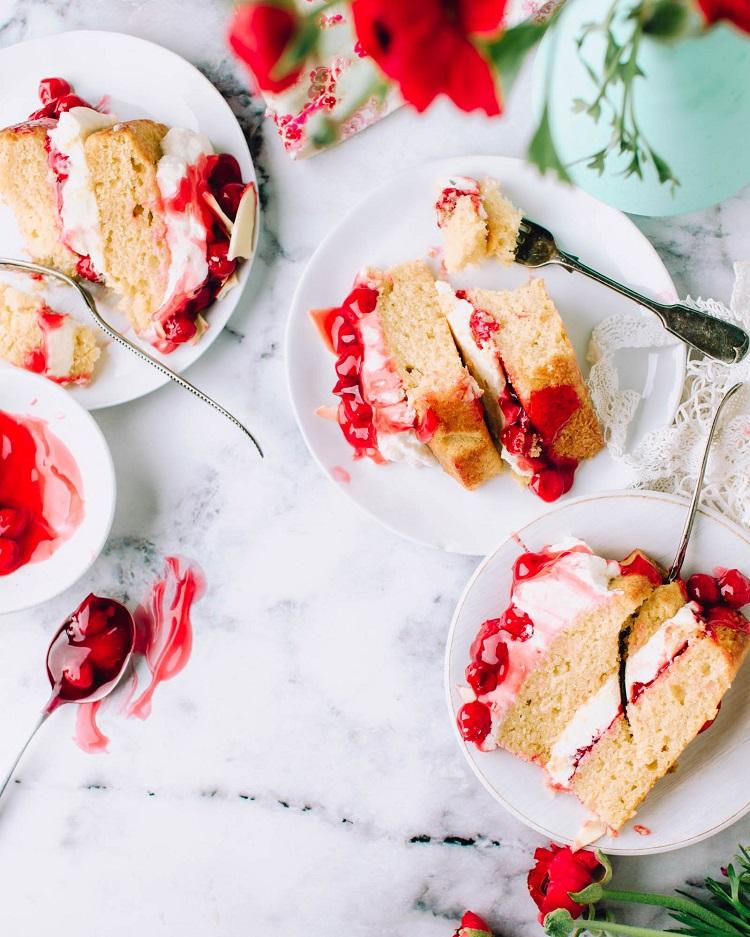 tasty vanilla and cherry cake slices on plates on table